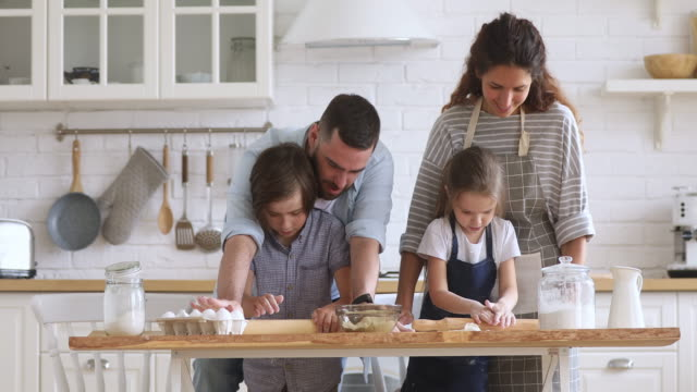 Happy parents and kids preparing dough with rolling pin together