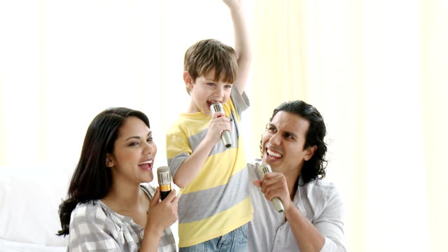 Happy parents doing a karaoke with their son video