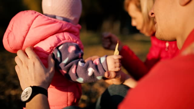 Happy parents give a child fallen leaves in the autumn field. video