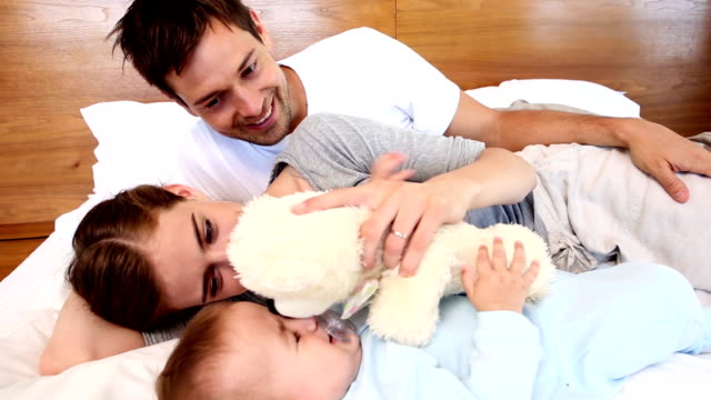 Happy parents lying on bed with baby son video