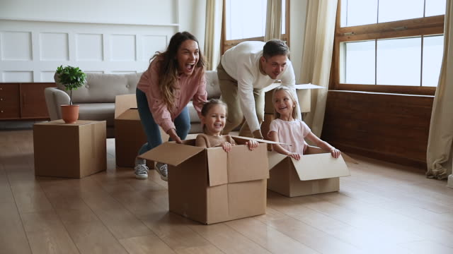 Happy parents pushing cardboard boxes with little kids, slow motion Funny active family playing on moving day, excited happy adult parents mom dad pushing cardboard boxes with cute little kids sit inside having fun packing relocate into new home concept, slow motion unpacking stock videos & royalty-free footage