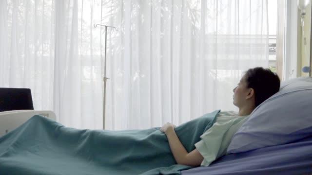 lycklig patient vila på sängen i sjukhuset församling rum. hälsovård och medicinskt koncept - hospital studio bildbanksvideor och videomaterial från bakom kulisserna
