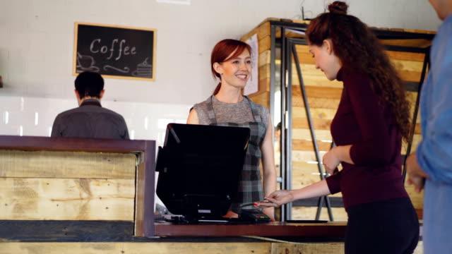 幸せな人は、朝のカフェでコーヒーを行くを購入するとき携帯電話で支払っています。食べ物や飲み物のサービス、新世紀と現代の技術コンセプト。 - 小売販売員点の映像素材/bロール