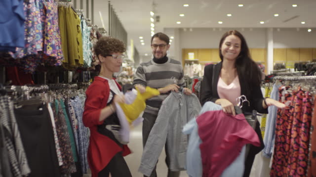 Happy People Dancing while Shopping in Clothing Store