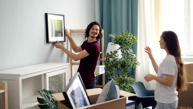 happy people decorating flat with picture choosing place talking and gesturing - decorare video stock e b–roll