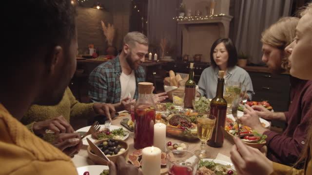 glückliche menschen essen abendessen und chatten - steak stock-videos und b-roll-filmmaterial