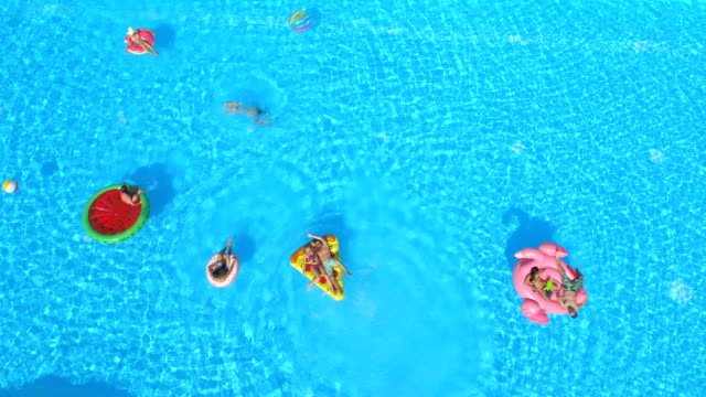 AERIAL: Happy people enjoying summer vacation on colorful floaties in pool water video