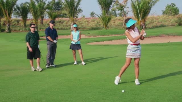 Feliz personas, amigos jugando en el club de golf, deportes, ocio, diversión - vídeo
