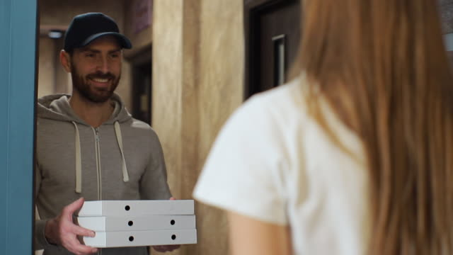 happy pizza delivery man visits home with boxes to a customer. giving money to worker and showing thumbs up. taking payment. - food delivery filmów i materiałów b-roll