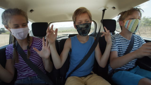 Happy playful kids travelling by car during the COVID-19 pandemic