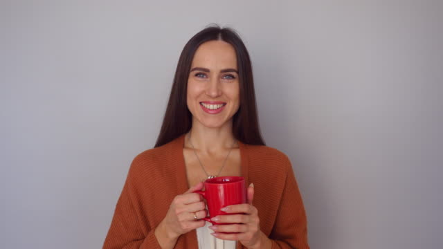 Happy pleased young woman taking a sip of coffee while holding a cup of aroma coffee in hands video