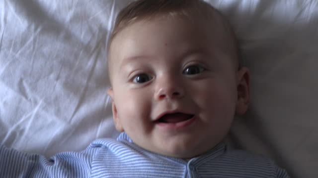 happy portrait of baby toddler lying in bed smiling laughing - 0 11 mesi video stock e b–roll