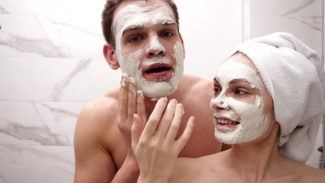 glad positiv ung par man och kvinna ha kul när du står i ett badrum efter dusch. båda lekfullt tillämpa vit mask på ansiktet. ha kul. porträttpar tillsammans applicera ansiktsmask - hälsosalong bildbanksvideor och videomaterial från bakom kulisserna