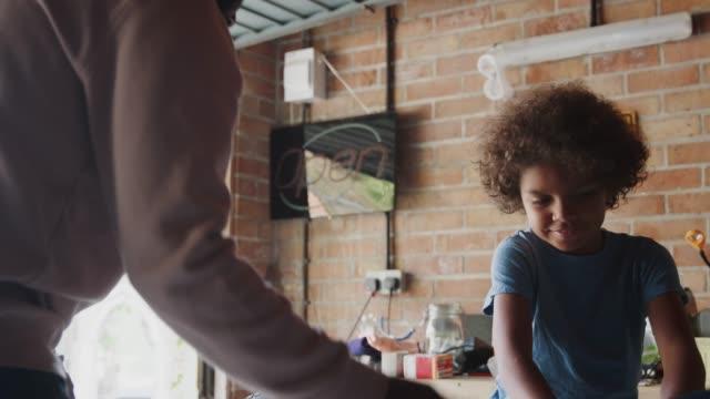 glücklich pre teen boy händeschütteln mit seinem vater zu feiern abschluss des builds ein renn-kart in ihrer garage, nahaufnahme, niedrigen winkel - garage stock-videos und b-roll-filmmaterial