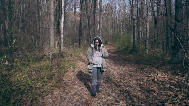 Happy pregnant woman caressing belly while strolling in forest video