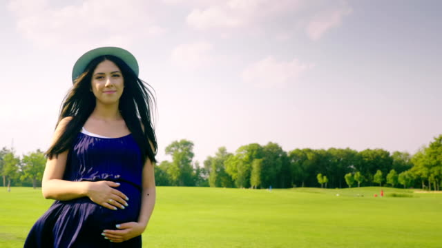 Happy pregnant woman is walking in the park, smiling video