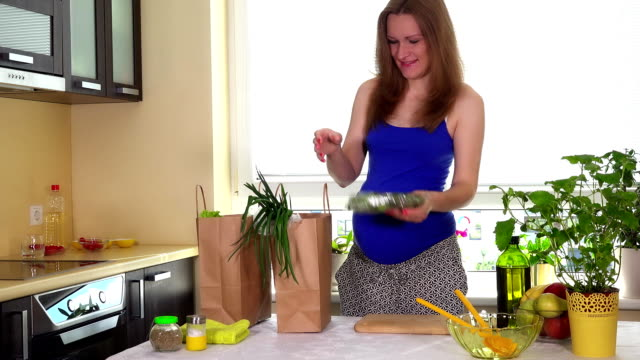 Happy pregnant woman unload paper bags with organic healthy vegetables video
