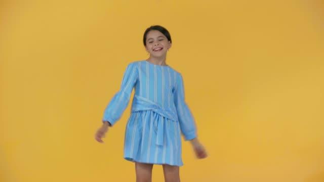黄色で孤立した青いドレスの幸せなプレティーンの子供 - 空白点の映像素材/bロール