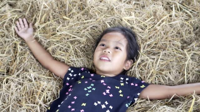 vidéos et rushes de heureuse jolie fille jouant avec une paille dans la grange - foin