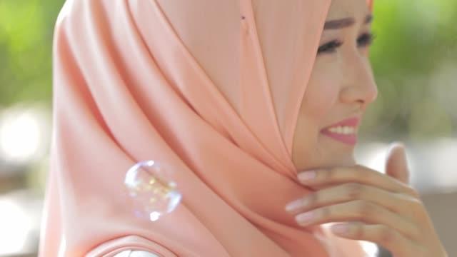 glad ganska muslimsk kvinna smile med hijab spelar bubbla på utomhus park - anständig klädsel bildbanksvideor och videomaterial från bakom kulisserna