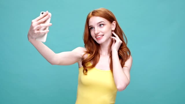 Happy pretty redheaded girl taking a selfie with mobile phone and making funny face while standing isolated over blue background video
