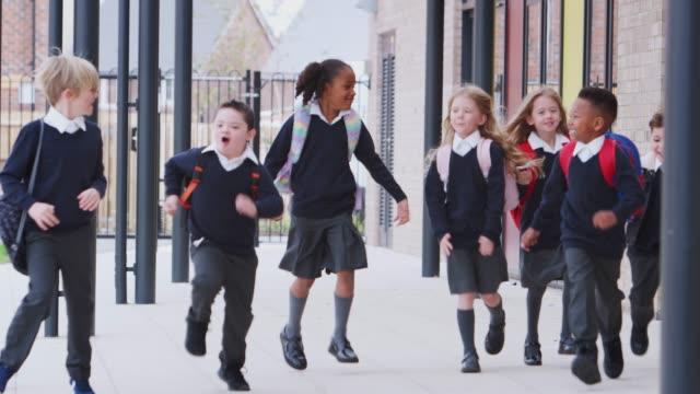 vidéos et rushes de gosses heureux d'école primaire dans des uniformes fonctionnant sur un passage à l'extérieur de leur bâtiment d'école, vue de face - uniforme