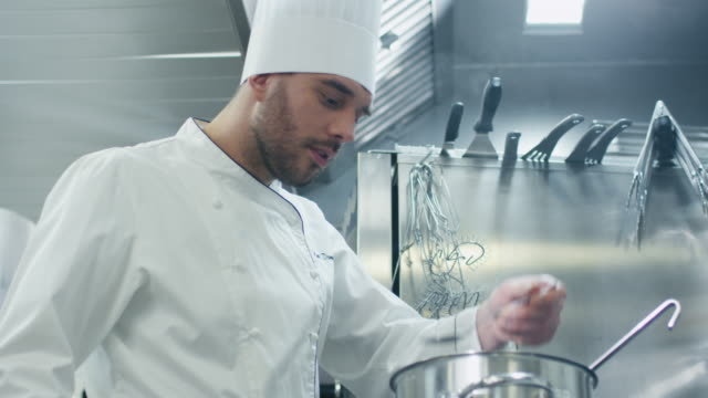 Happy professional chef in a commercial kitchen in a restaurant or hotel is tasting soup. video