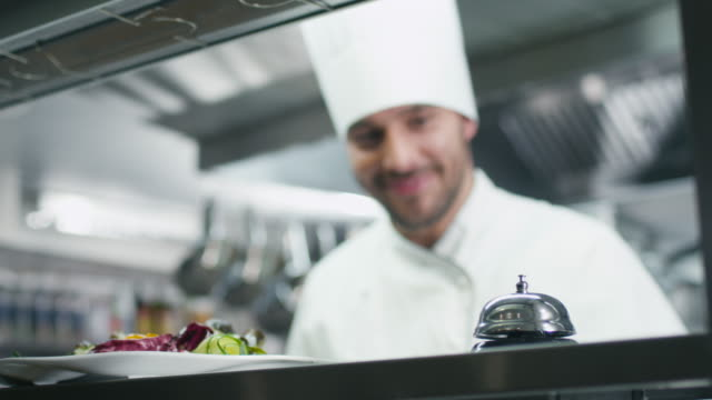 Happy professional chef in a commercial kitchen in a restaurant or hotel is serving salad. video
