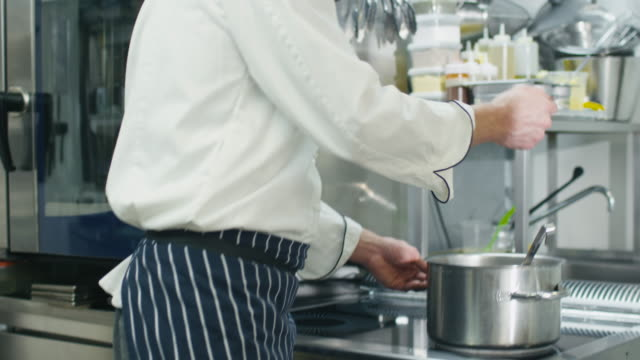Happy professional chef in a commercial kitchen in a restaurant or hotel is tasting soup. Happy professional chef in a commercial kitchen in a restaurant or hotel is tasting soup. tasting stock videos & royalty-free footage