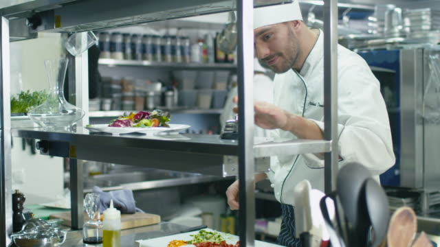 Happy professional chef in a commercial kitchen is garnishing and serving salad. video