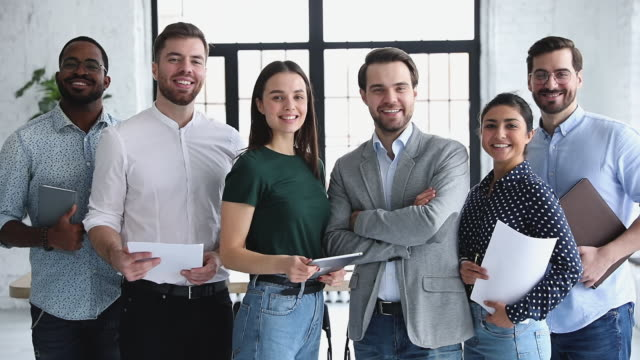 Happy professional multiethnic business team people smiling looking at camera Happy proud confident professional multiethnic business people leaders employees company staff diverse people group smiling looking at camera standing in office together, corporate team portrait employee stock videos & royalty-free footage