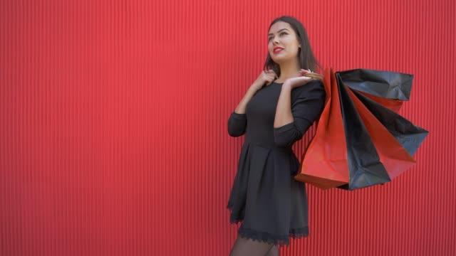 vídeos y material grabado en eventos de stock de felices compras, mujer reflexiva con muchas bolsas piensa qué comprar con descuento en negro el viernes - black friday sale