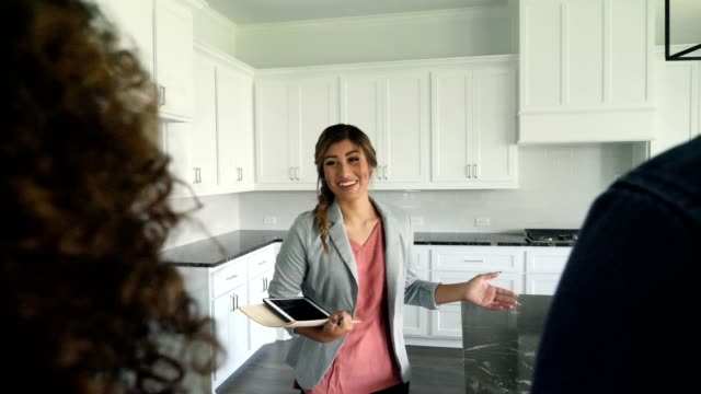 Happy real estate agent shows home to potential clients