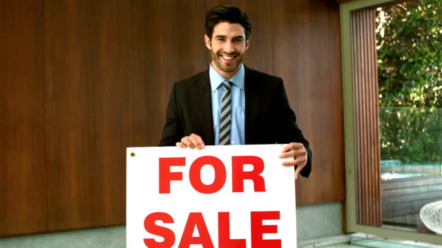 Happy real estate agent with sold sign video