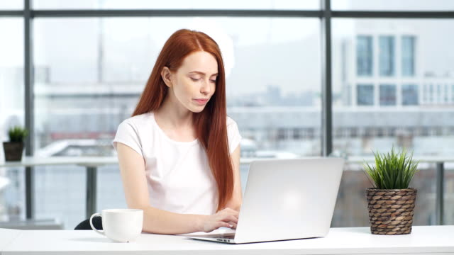 happy redhead girl working at laptop in office - touchpad video stock e b–roll