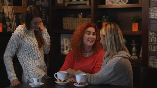 Happy redhead woman being surprised with gift box from her female friends. video