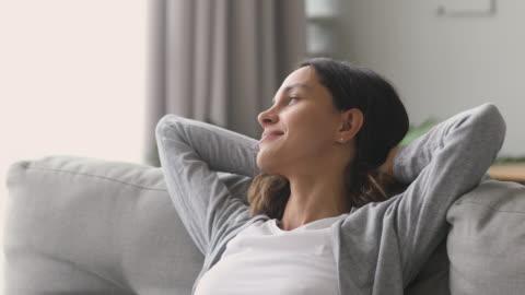 szczęśliwa zrelaksowana kobieta odpoczywa na kanapie cieszyć spokojny dzień - relaks filmów i materiałów b-roll
