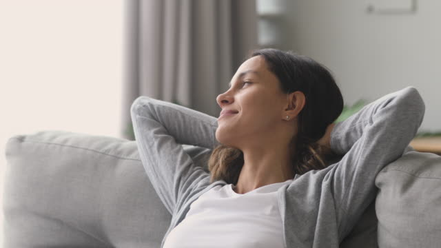 Happy relaxed woman rest lounge on couch enjoy peaceful day Happy relaxed young woman rest lounge lean on couch enjoy peaceful mood, healthy lazy calm girl dreaming breathing fresh air sit on comfortable sofa in living room on stress free cozy day at home mindfulness stock videos & royalty-free footage
