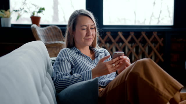 happy relaxed young attractive blonde freelancer woman shopping online using smartphone app on self isolation at home. - divano procrastinazione video stock e b–roll