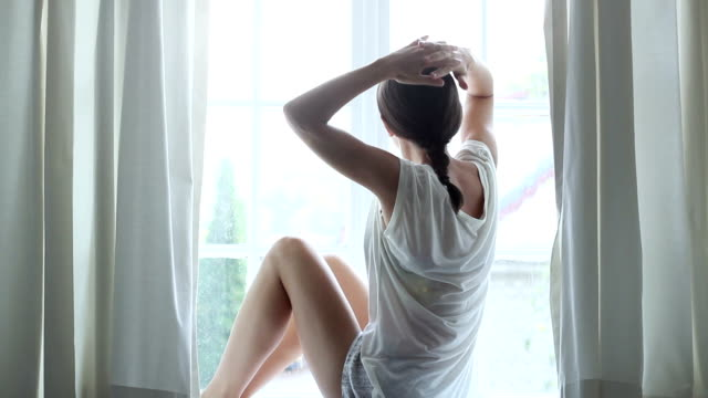 Happy relaxed young woman sits by a window video