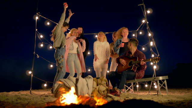 happy rest, group of young people dancing and singing near campfire on beach in lighting of garlands - video
