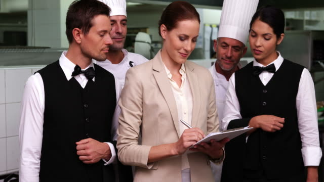 Happy restaurant staff with manager smiling at camera Happy restaurant staff with manager smiling at camera in a commercial kitchen wait staff stock videos & royalty-free footage