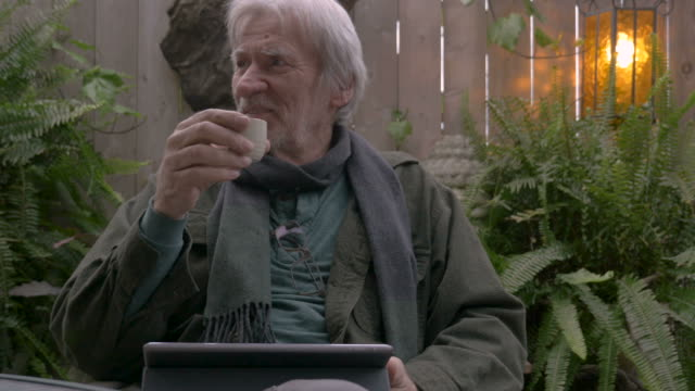 Happy retired man laughing and drinking sake using his digital tablet video
