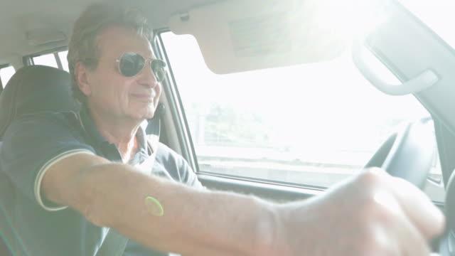 Happy retraité âgé tenant le volant et la conduite sur route en 4K - Vidéo
