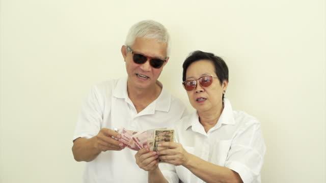Intensos tonos senior feliz asiática con gran cantidad de dinero en efectivo. Tirar el dinero en el aire - vídeo