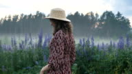 istock Happy romantic girl in a dress and hat walks along the field with flowers and fog, dances inspired and looks dreamily around 1253980981