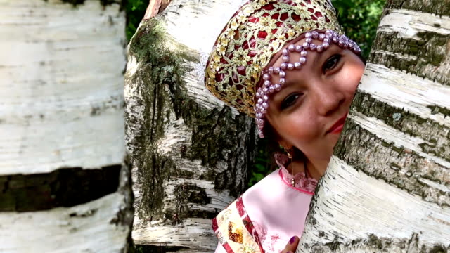 Happy russian girl in folk costume and birch video
