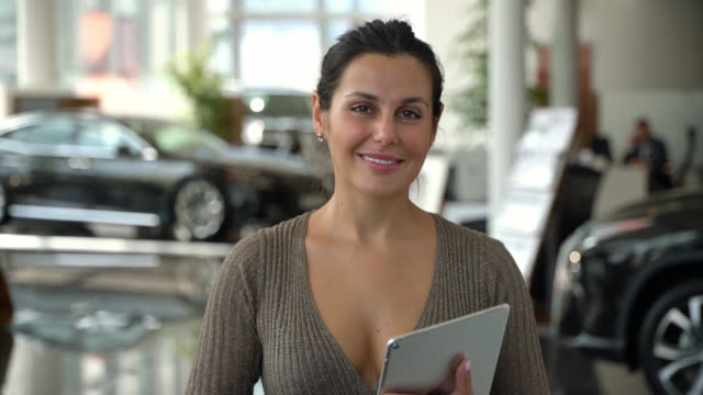 Happy sales woman working at a car dealership smiling at camera Beautiful happy sales woman working at a car dealership smiling at camera car shopping stock videos & royalty-free footage
