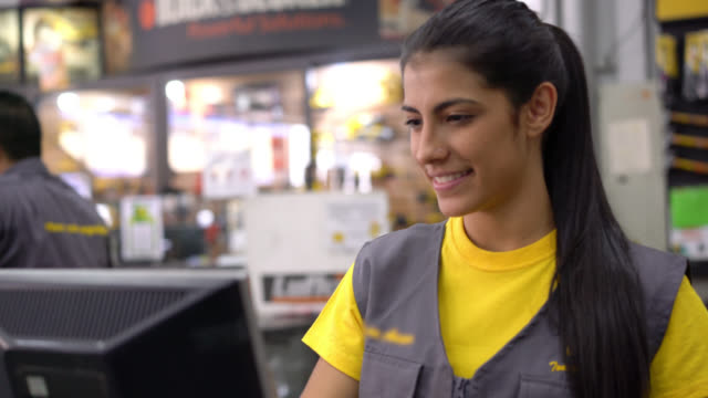 Happy saleswoman working at a hardware store smiling video
