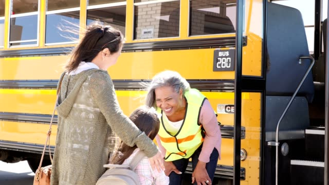 happy school bus driver talks with little girl and her mom before the girl boards the bus - bus driver stock videos and b-roll footage